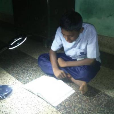 Inmate Using The Solar Table Lamp To Study