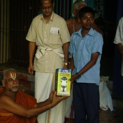 Swamigal Presenting Solar Lantern To The Student Of The Village School
