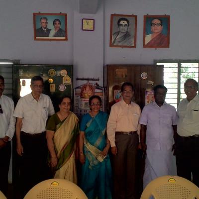 Guests Standing Below The Photos Of The Founders Of Balar Illam
